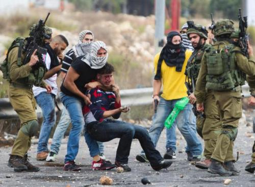 Undercover Israeli officers detain wounded Palestinian protester near Ramallah, October 7th (photo: Majdi Mohammed/Associated Press)